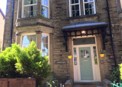 Cream sliding sash windows. Fiberglass door with side screens and top light