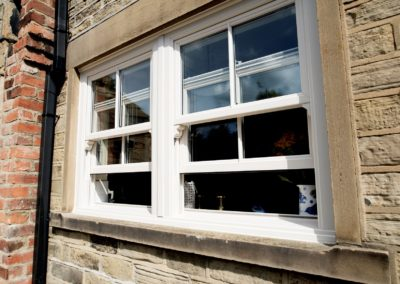 vertical sliding sash windows with plant on sash horns